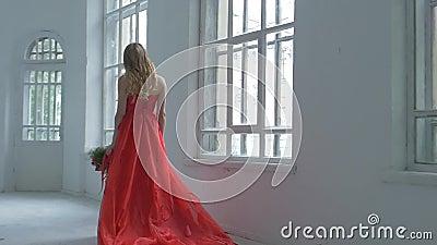 华美的红色礼服的俏丽的女孩走通过的 股票视频