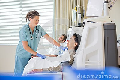 护士tube_examined医生的 使用数字式片剂的护士在病区 adjusting tube in