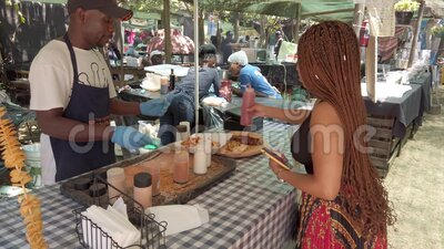 南非约翰内斯堡Fourways Farmers Market的摊位上的妇女购买和吃当地食物 股票视频