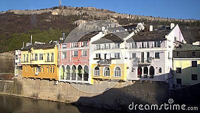 历史的五颜六色的修造的门面在一好日子在洛维奇,保加利亚 前面的奥瑟姆河河和山在背景中 影视素材