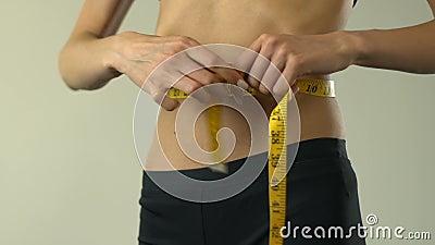 厌食有磁带线路和显示的女孩测量的腰部好,不可靠 影视素材