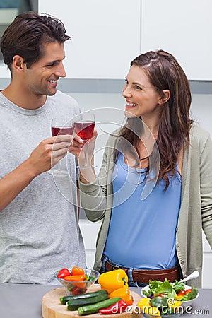 可爱的夫妇使叮当响的杯红葡萄酒