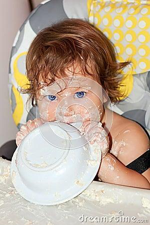 吃酸奶和被弄脏的表面的婴孩