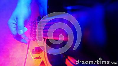 吉他弹奏者在他的在明亮的霓虹照明设备的吉他使用 烟机器起动运转,并且屋子用烟填满 影视素材