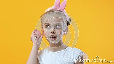 听逗人喜爱的头饰带的俏丽的女孩震动鸡蛋和听起来,乐趣 股票录像