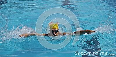 水池的年轻男孩游泳者,蝶泳
