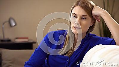 哀伤,沮丧的少妇坐沙发 消极情感和感觉概念 影视素材