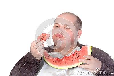 品尝片式西瓜的肥胖人