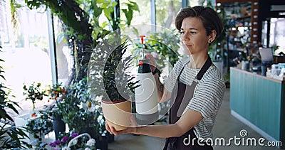 喷洒罐的围裙的可爱的年轻浅黑肤色的男人绿色植物使用喷水隆头 股票录像
