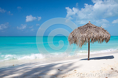 在一个完善的白色海滩的沙滩伞在海前面