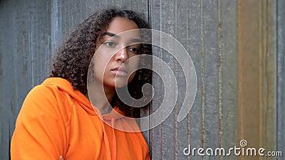 在城市环境中,身着橙色连帽衫的黑人少女 股票录像