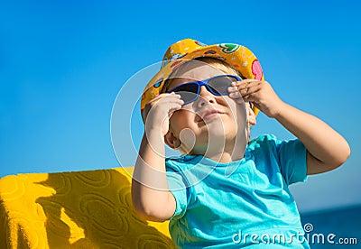 在太阳镜和帽子的男孩孩子在反对蓝天的海滩.图片