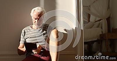 在家使用在地板4k上的老人数字式片剂 股票视频