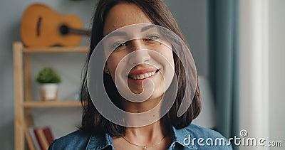 在家微笑年轻女人的特写镜头的慢动作转向照相机和 股票视频