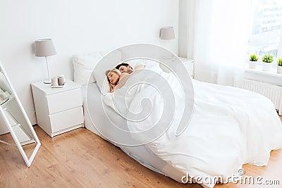人们,休息和关系概念 愉快的夫妇在家睡觉在床上.