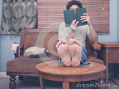 一个赤足年轻人在家休息他的在咖啡桌上的腿,当读时,有在沙发的一只图片