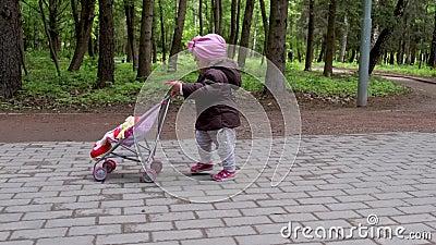 在春园里带着婴儿车玩具走路的女婴