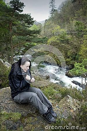 在河感觉寒冷附近的女性远足者