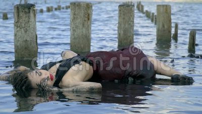 在泥抹上的身体苗条金发碧眼的女人和在从被毁坏的盐水池的木岗位附近弄湿了礼服谎言在出海口 股票视频