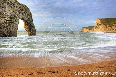 在海洋的充满活力的日出有在前景的岩石栈的