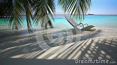 在热带海滩的被忘记的海滩睡椅在海浪 股票录像
