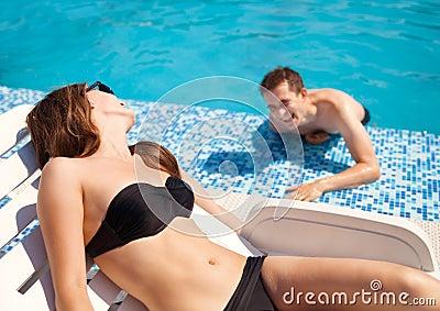 在爱的夫妇在游泳池附近