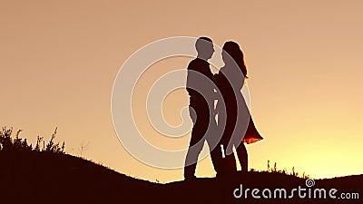 在爱跳舞剪影的夫妇在日落自然和亲吻 爱恋的男人和妇女有狗跳舞的现出轮廓慢 影视素材