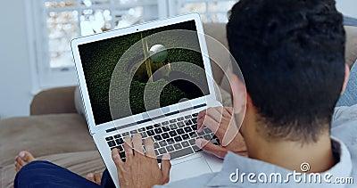 在膝上型计算机的人观看的高尔夫球在客厅 影视素材