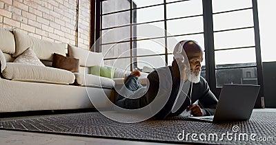 在膝上型计算机的老人听的音乐在客厅4k 股票视频