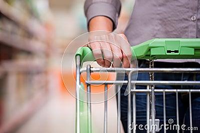 在超级市场的妇女购物有台车的