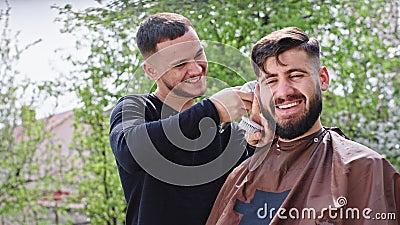 在镜头前,一位理发师在花园里给家里的朋友做专业理发,他们笑着 影视素材