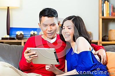 在长沙发的亚洲夫妇有片剂个人计算机的