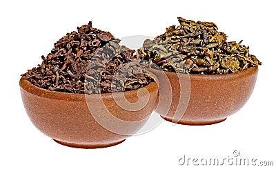在黏土杯子的干黑色和绿茶