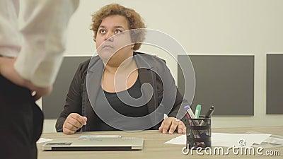 坐在办公室睡觉的桌上的肥满疲乏的妇女 来到书桌的一个无法认出的上司,和 股票录像