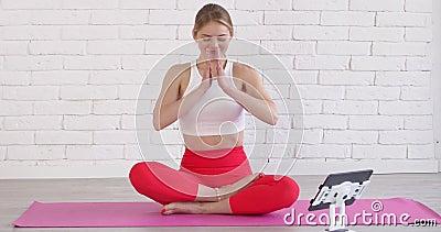 坐在垫子上、双腿交叉、看瑜伽在线课的美丽运动女 影视素材