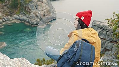 坐在峭壁边缘的旅游女孩在盐水湖和享受美丽的景色 股票录像