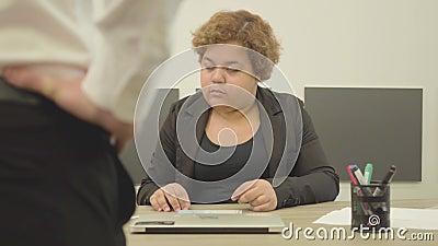 坐在桌上的肥满妇女在办公室 走向书桌和妇女的一个无法认出的人举手  影视素材