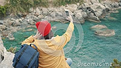 坐在盐水湖和射击的selfie的峭壁边缘的旅游女孩 影视素材