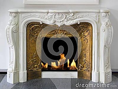 在白色大理石的土气样式壁炉与金子.图片