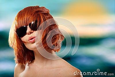 夏天青少年的女孩红发快乐在太阳镜