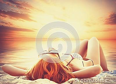 太阳镜的美丽的女孩在海滩.在日落时间.图片