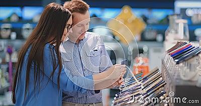 夫妇选择在一个电存储器的一个手机 与智能手机的陈列室 股票视频