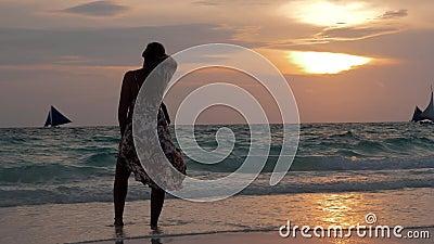 女人赤脚站在沙滩上,穿着风中飘扬的夏装,看上去美丽的日落 生活女性 影视素材