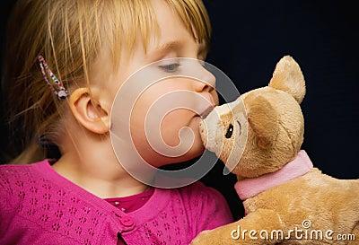 女孩亲吻玩具熊