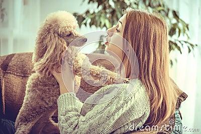 女孩在家休息与在扶手椅子的一条狗.图片