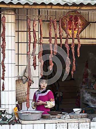 女孩出售年轻人的hani香肠 图库摄影片