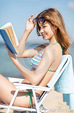 女孩在海滩睡椅的阅读书