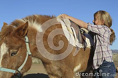 女孩小马备鞍的年轻人