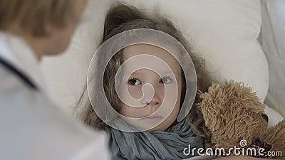 女性医生谈话与在家在床上的不适的哭泣的女孩,医疗保健 影视素材