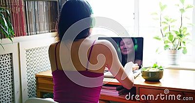 妇女听的歌曲背面图,当使用膝上型计算机时 股票录像